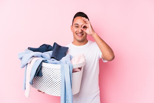 Młody łaciński mężczyzna podnosi up brudni ubrania odizolowywał z podnieceniem utrzymuje ok gest na oku.