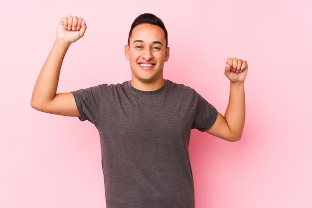 Młody łaciński mężczyzna pozuje w różowej ścianie świętuje wyjątkowy dzień, skacze i energicznie podnosi ręce.