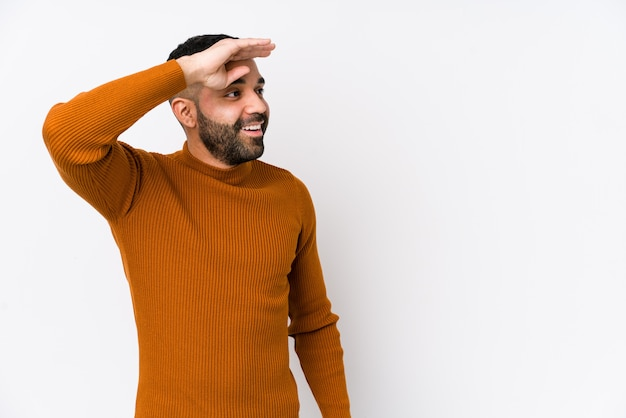 Młody łaciński mężczyzna przeciw białej ścianie odizolowywał patrzeć daleki utrzymujący rękę na czole.