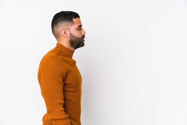 Młody łaciński mężczyzna przeciw białej ścianie odizolowywał patrzeć w lewo, z ukosa pozę.