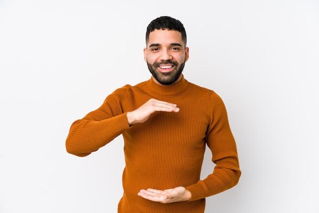 Młody łaciński mężczyzna przeciw białej ścianie odizolowywał trzymający coś obiema rękami, prezentacja produktu.