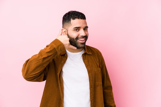 Młody łaciński mężczyzna przeciw różowej ścianie odizolowywał pokazywać gesta telefonu komórkowego gesta palcami.