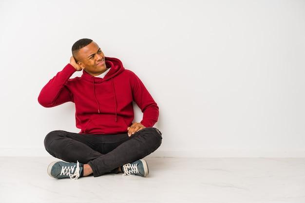 Młody łaciński mężczyzna siedzi na podłodze na białym tle dotykając tyłu głowy, myśląc i dokonując wyboru.