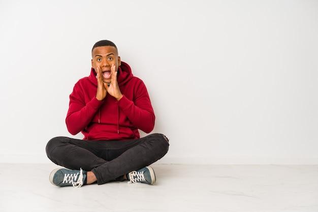Młody łaciński mężczyzna siedzi na podłodze na białym tle krzycząc podekscytowany do przodu.