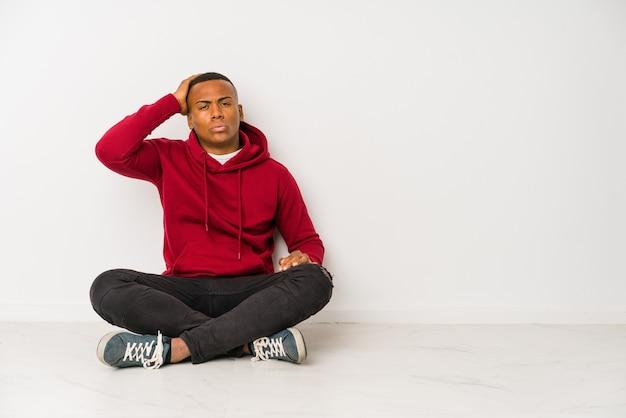 Młody łaciński mężczyzna siedzi na podłodze na białym tle zmęczony i bardzo senny trzymając rękę na głowie.