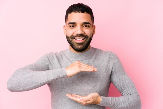 Młody łaciński mężczyzna trzyma coś obiema rękami, prezentacja produktu
