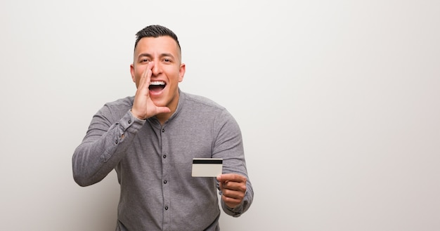 Młody łaciński mężczyzna trzyma kartę kredytową krzyczy coś szczęśliwego z przodu