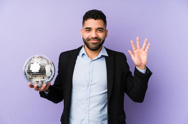 Młody łaciński mężczyzna trzyma piłkę imprezową na białym tle młody łaciński mężczyzna trzyma wafel na białym tle uśmiechnięty wesoły pokazując numer pięć palcami. <mixto>