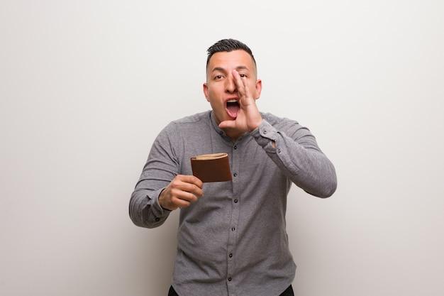 Młody łaciński mężczyzna trzyma portfel krzyczy coś szczęśliwego z przodu
