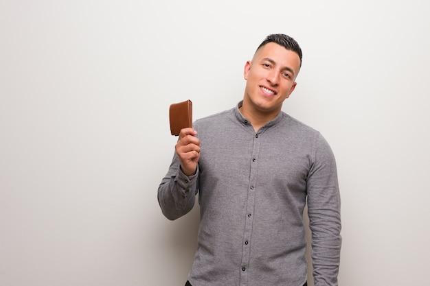 Młody łaciński mężczyzna trzyma portfel rozochocony z dużym uśmiechem