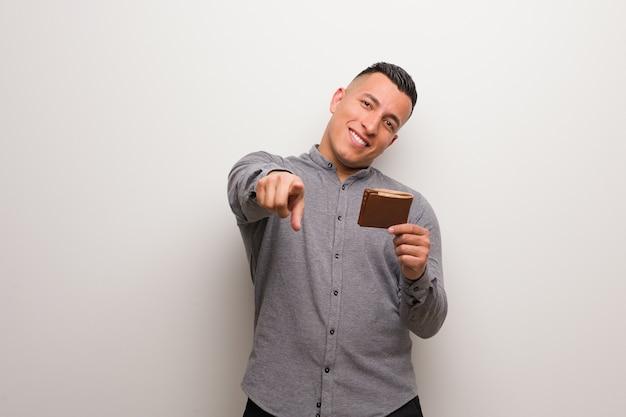 Młody łaciński mężczyzna trzyma portfel wesoły i uśmiechnięty, wskazując na przód