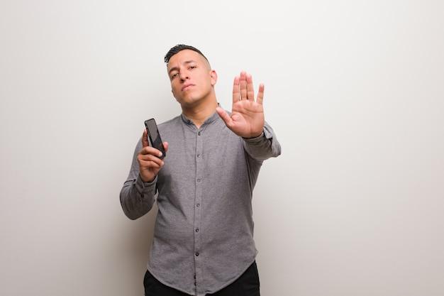 Młody łaciński mężczyzna trzyma telefon stawia rękę w przód