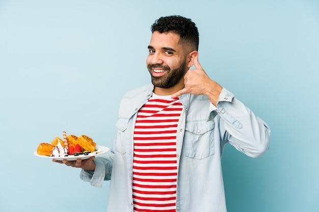 Młody łaciński mężczyzna trzyma wafel na białym tle przedstawiający gest rozmowy telefonicznej palcami.