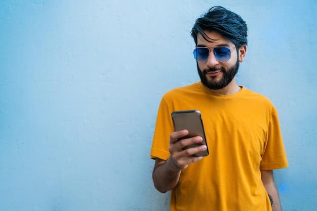Młody łaciński mężczyzna używa jego telefon komórkowego.