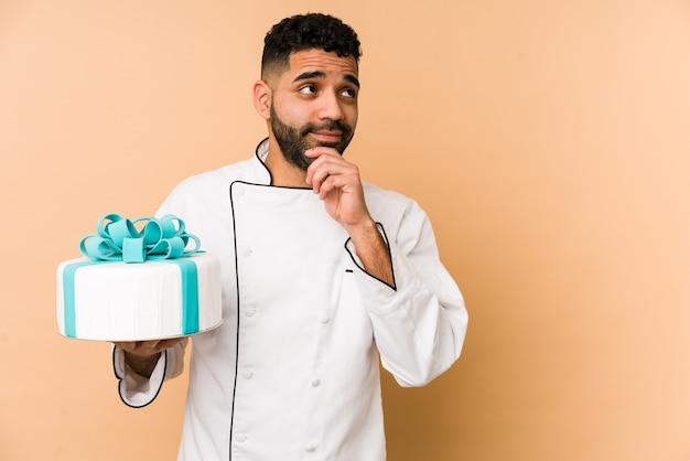 Młody łaciński piekarz mężczyzna trzyma tort