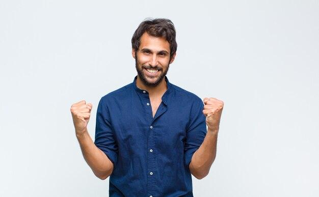Młody łaciński przystojny mężczyzna czuje się szczęśliwy, pozytywny i odnoszący sukcesy, świętuje zwycięstwo, osiągnięcia lub powodzenia