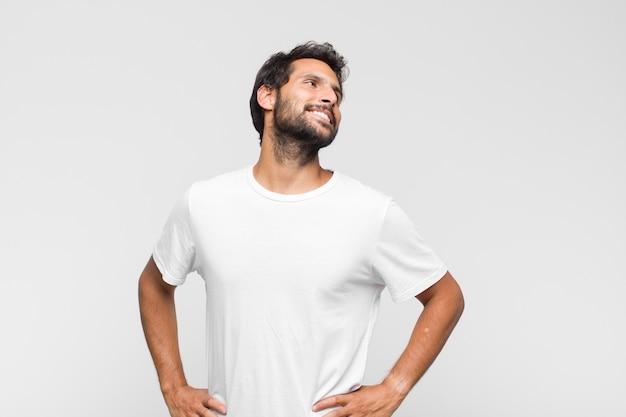 Młody łaciński przystojny mężczyzna wyglądający na szczęśliwego, wesołego i pewnego siebie, uśmiechającego się dumnie i patrząc na bok z obiema rękami na biodrach