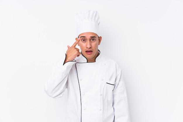 Młody łaciński szefa kuchni mężczyzna odizolowywający pokazywać rozczarowanie gest z palcem wskazującym.