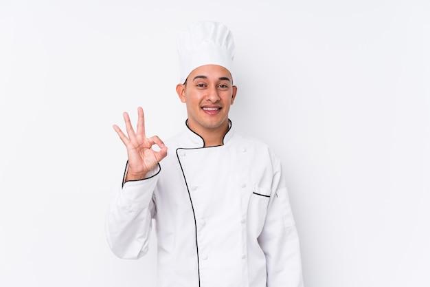 Młody łaciński szefa kuchni mężczyzna rozochocony i ufny pokazuje ok gest.