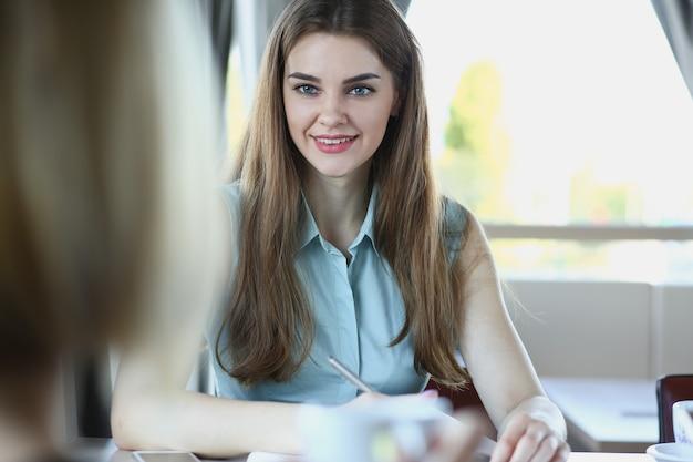 Młody ładny biznes ledy siedzi w kawiarni mówić napisać koncepcję