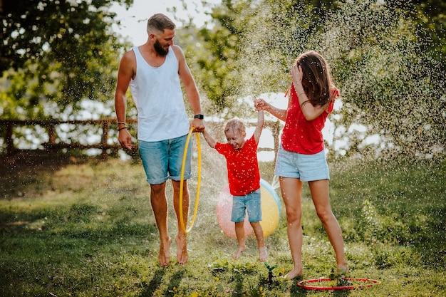 Młody ładny boso trzyosobowa rodzina w letnie spodenki jeansowe zabawy na zielonym trawniku w pobliżu rozpryskiwania piłki wodnej. szczęście.