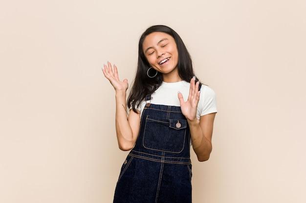 Młody ładny chiński nastolatek młoda blond kobieta ubrana w płaszcz przed różowy radosny śmiech dużo. koncepcja szczęścia.