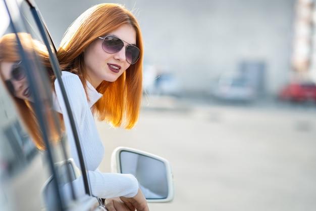 Młody ładny kobieta kierowca w okularach przeciwsłonecznych przyglądających przednie okno samochodu w słoneczny letni dzień.