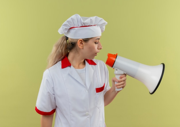Młody ładny kucharz w mundurze szefa kuchni patrząc w dół i rozmawiając przez głośnik na białym tle na zielonym tle