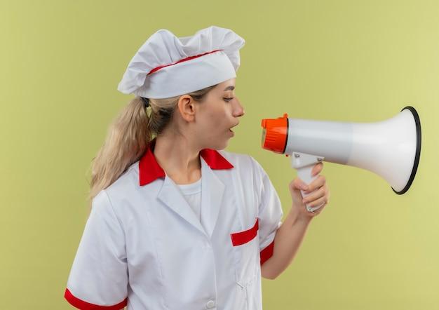 Młody ładny kucharz w mundurze szefa kuchni rozmawia przez głośnik patrząc na bok na białym tle na zielonym tle