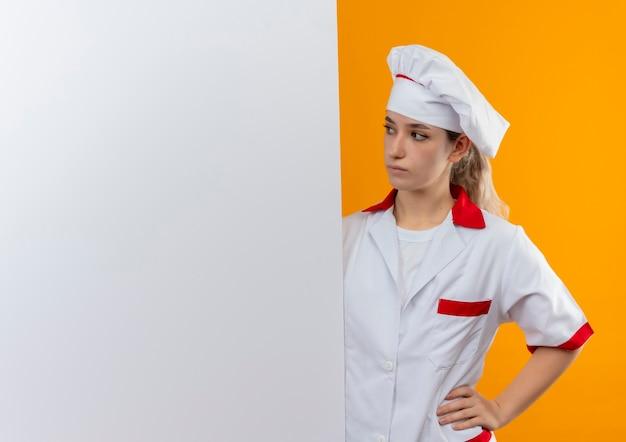 Młody ładny kucharz w mundurze szefa kuchni stojący z tyłu i patrząc na białą ścianę ręką na talii