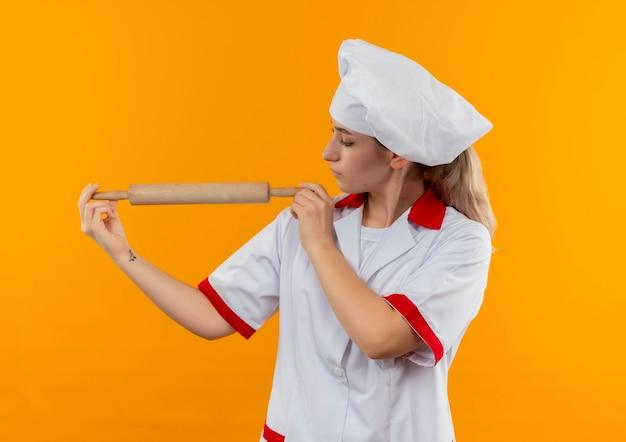 Młody ładny kucharz w mundurze szefa kuchni, trzymając i patrząc na wałek do ciasta