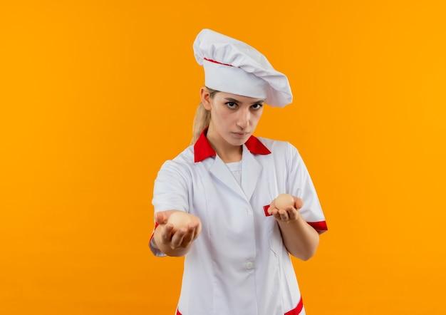 Młody ładny kucharz w mundurze szefa kuchni, trzymając i wyciągając jajka patrząc