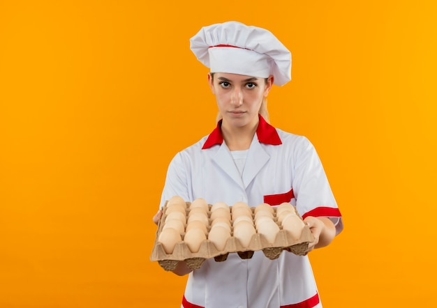 Młody ładny kucharz w mundurze szefa kuchni trzymając karton jaj szuka
