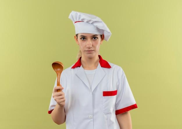 Młody ładny kucharz w mundurze szefa kuchni trzymając łyżkę i patrząc na białym tle na zielonym tle