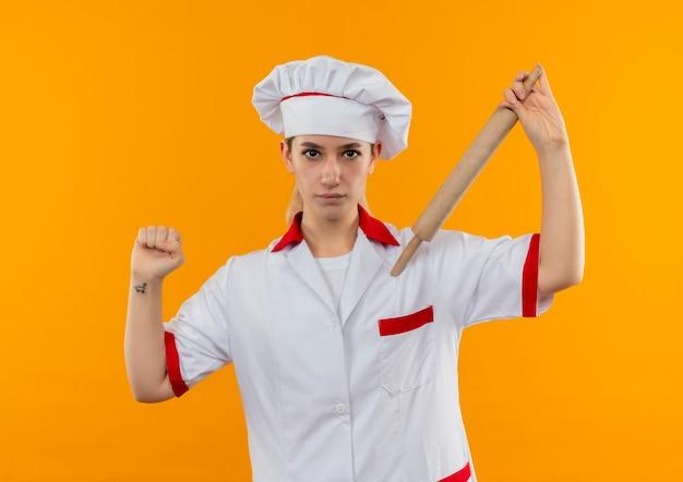 Młody ładny kucharz w mundurze szefa kuchni trzymając wałek do ciasta i ściskającą pięść patrząc
