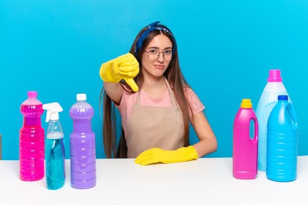 Młody, ładny opiekun domu czuje się zły, zły, zirytowany, rozczarowany lub niezadowolony, pokazując kciuki w dół z poważnym spojrzeniem