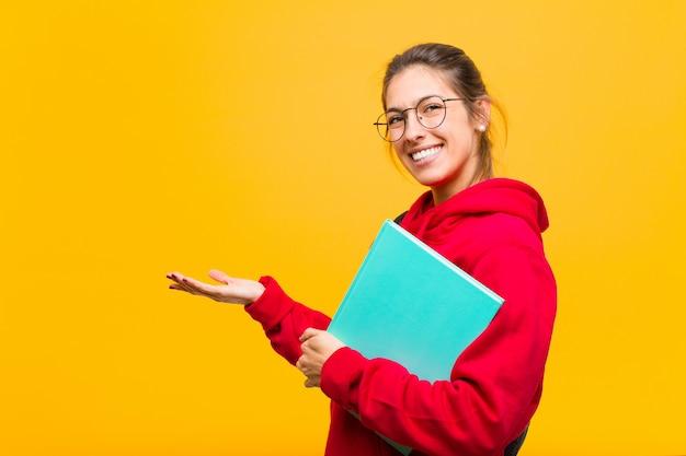 Młody ładny studencki ono uśmiecha się radośnie, czuje się szczęśliwy i pokazuje pojęcie w kopii przestrzeni z palmą ręka
