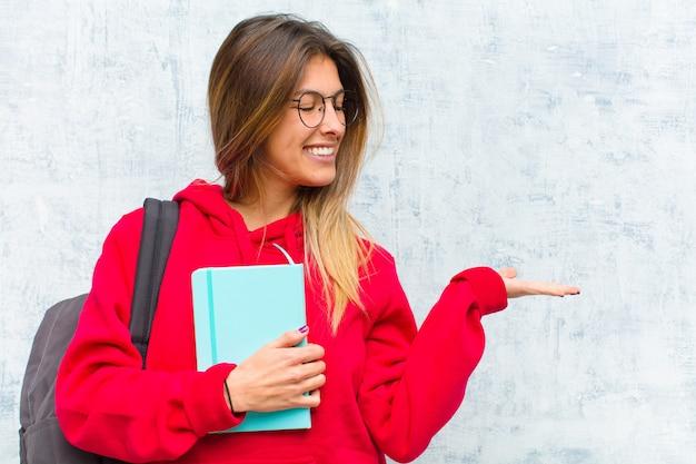 Młody ładny uczeń czuje się szczęśliwy i uśmiechnięty od niechcenia, patrząc na obiekt lub pojęcie trzymane na ręce na stronie