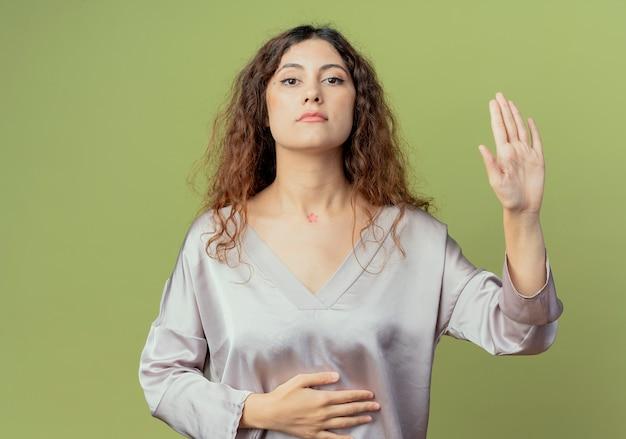 Młody ładny żeński pracownik biurowy kładąc rękę na brzuchu i pokazując gest stopu na białym tle na oliwkowej ścianie
