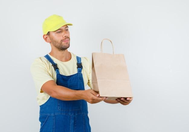 Młody ładowacz dostarczający papierową torbę i uśmiechnięty w jednolitym widoku z przodu.