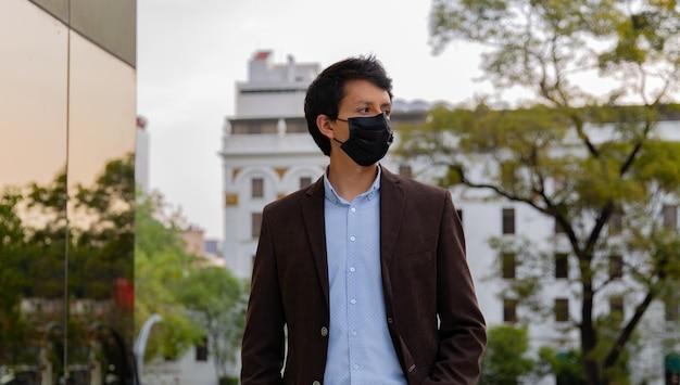 Młody latynos noszący maskę ze względów ochronnych podczas pandemii zakaźnej