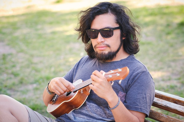 Młody latynos siedzi na krześle w parku, grając na ukulele