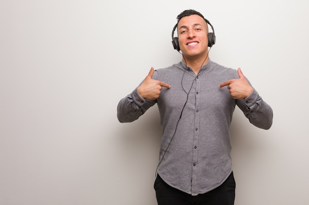 Młody latynos słuchający muzyki jest zaskoczony, czuje się dobrze i odnosi sukcesy
