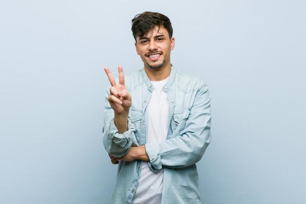 Młody latynoski fajny mężczyzna pokazuje numer dwa z palcami.