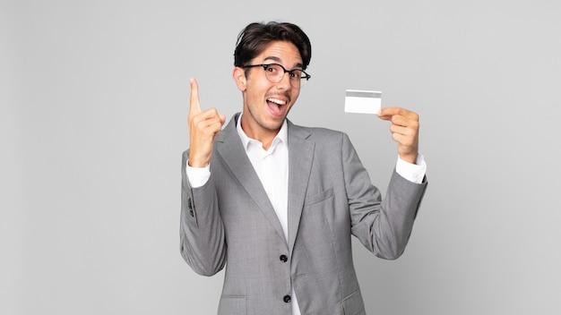 Młody latynoski mężczyzna czuje się jak szczęśliwy i podekscytowany geniusz po zrealizowaniu pomysłu i trzymaniu karty kredytowej