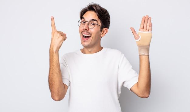 Młody latynoski mężczyzna czuje się jak szczęśliwy i podekscytowany geniusz po zrealizowaniu pomysłu. koncepcja bandaża ręcznego
