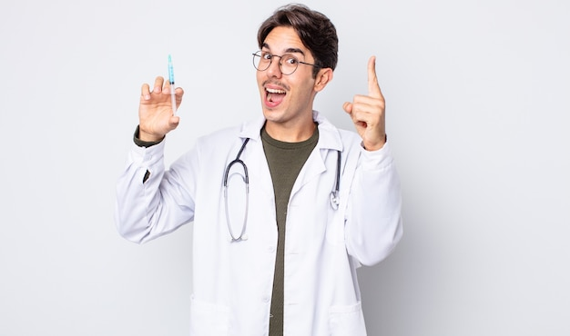 Młody latynoski mężczyzna czuje się jak szczęśliwy i podekscytowany geniusz po zrealizowaniu pomysłu. koncepcja strzykawki lekarza