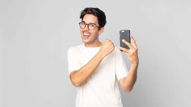 Młody latynoski mężczyzna czuje się szczęśliwy i staje przed wyzwaniem lub świętuje i trzyma smartfon