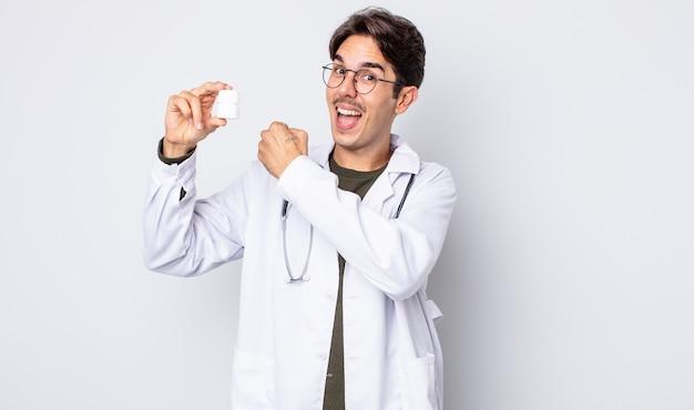 Młody latynoski mężczyzna czuje się szczęśliwy i stoi przed wyzwaniem lub świętuje. lekarz z koncepcją butelki tabletek