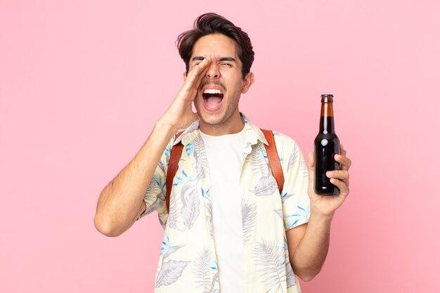 Młody latynoski mężczyzna czuje się szczęśliwy, wydając wielki okrzyk z rękami przy ustach i trzymając butelkę piwa